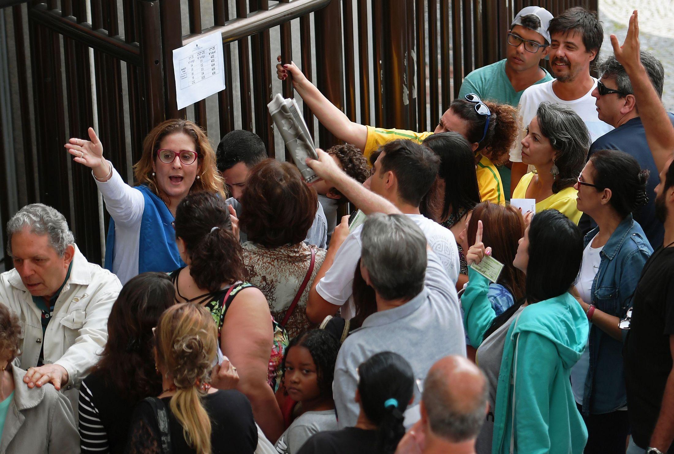 Representante da Justiça Eleitoral orienta eleitores em Copacabana, no Rio de Janeiro. (Foto: CARL DE SOUZA / AFP)